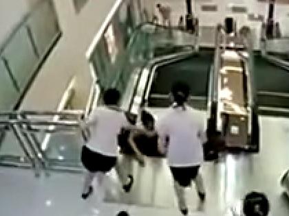 Женщина успела вытолкать сына на руки сотрудникам ТЦ перед самым падением // Кадр YouTube