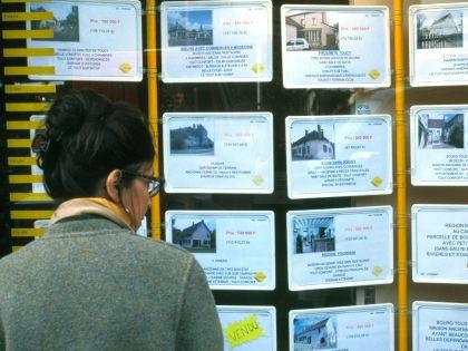 Женщина возле стенда с объявлениями о продаже недвижимости // Pascal Deloche/Global Look
