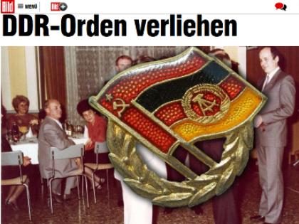 В центре фото — знак Общества дружбы ГДР и СССР, за ним справа — Путин, слева в белом костюме — мужчина, который вручает Путину, вероятно, именно такой знак // Скриншот сайта Bild