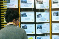 Женщина возле стенда с объявлениями о продаже недвижимости