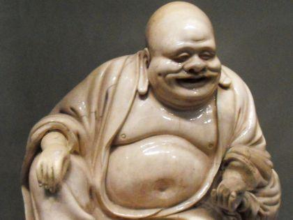 На столе размещена фигурка Хотея – бога, приносящего богатство