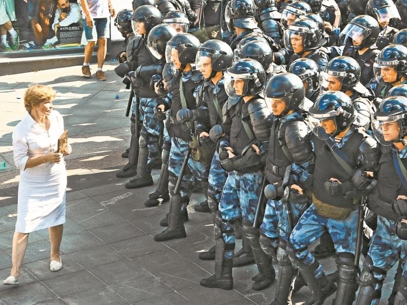 Женщина перед цепью сотрудников правопорядка в центре Москвы 27 июля // фото: Андрей Струнин / Sobesednik.ru