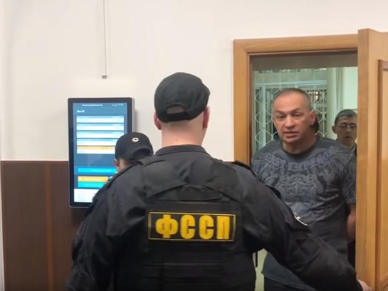Александр Шестун под конвоем покидает одно из судебных заседаний // стоп-кадр / Youtube