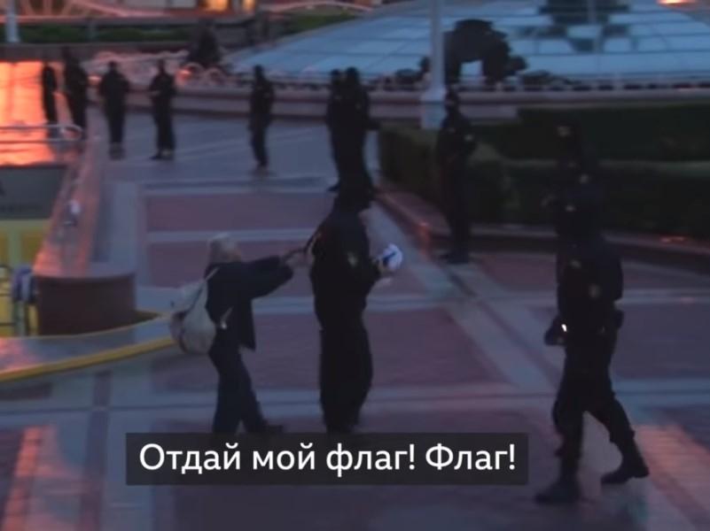 Нина Багинская пытается отнять у омоновца свой флаг на одной из акций // Скриншот с видео на YouTube
