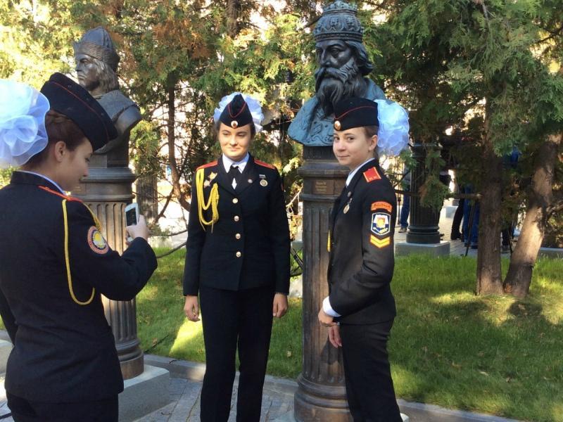 Девочки-кадеты, довольные, фотографируются с насаженным на постамент бюстом царя и хихикают